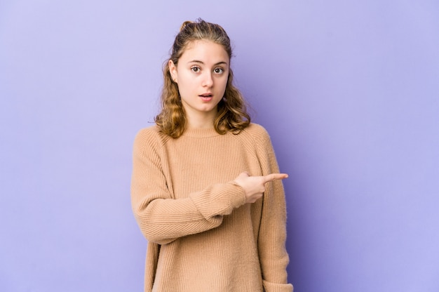 Young caucasian woman on purple pointing to the side Premium Photo