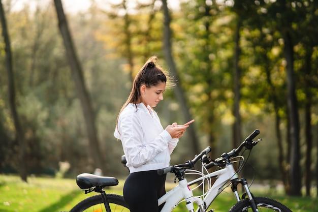 Молодая женщина кавказской, отдыхая в парке, использует мобильный телефон. Бесплатные Фотографии