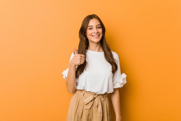 Young caucasian woman smiling and raising thumb up Premium Photo