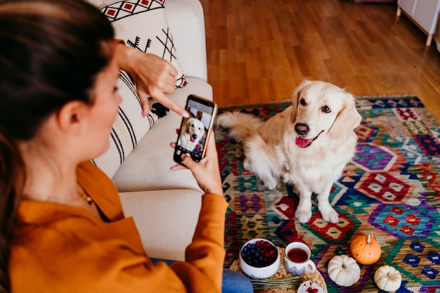 Young caucasian woman taking a picture of her golden retriever dog with mobile phone Premium Photo