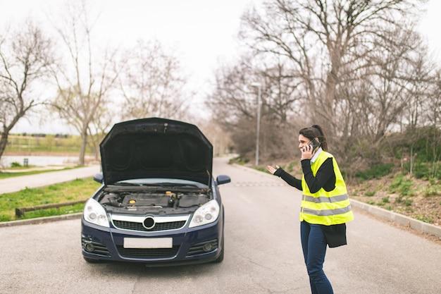 Молодая кавказская женщина, говоря на ее сотовом телефоне пока ее автомобиль сломан на дороге концепция автомобиля и придорожной помощи. Premium Фотографии