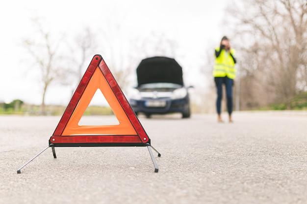 Молодая женщина кавказской, говорить на свой мобильный телефон, в то время как ее автомобиль сломался на дороге с светоотражающие предупреждающие треугольники. выборочный фокус. концепция автомобильной и придорожной помощи. Premium Фотографии