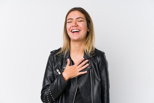 Молодая кавказская женщина в черной кожаной куртке громко смеется, держа руку на груди. Premium Фотографии