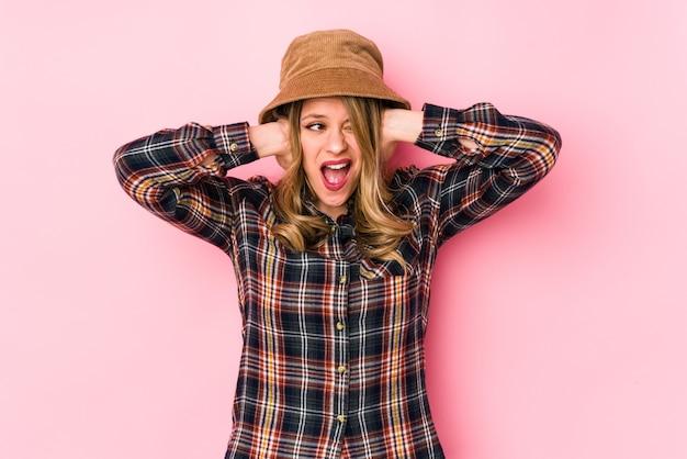 Молодая кавказская женщина в шляпе изолировала уши руками, пытаясь не слышать слишком громкий звук. Premium Фотографии