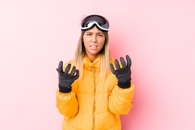 Молодая кавказская женщина в лыжной одежде в розовой стене расстроена и кричит напряженными руками. Premium Фотографии