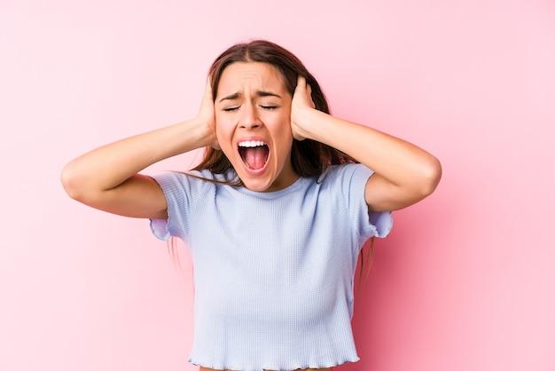 Молодая кавказская женщина в лыжной одежде изолировала конические уши руками, пытаясь не слышать слишком громкий звук. Premium Фотографии
