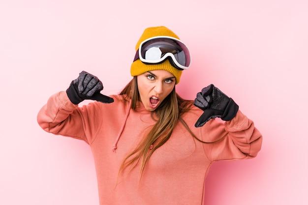 Молодая кавказская женщина в лыжной одежде изолировала, показывая большой палец вниз и выражая неприязнь. Premium Фотографии