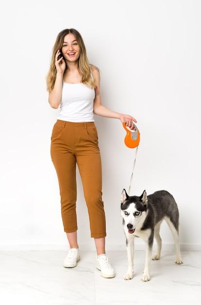 孤立した壁の上の犬を持つ若い白人女性 Premium写真
