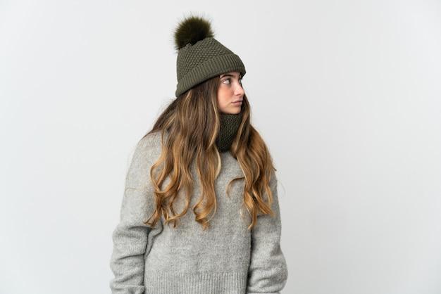 겨울 모자 측면을 찾고 흰색 배경에 고립 된 젊은 백인 여자 프리미엄 사진