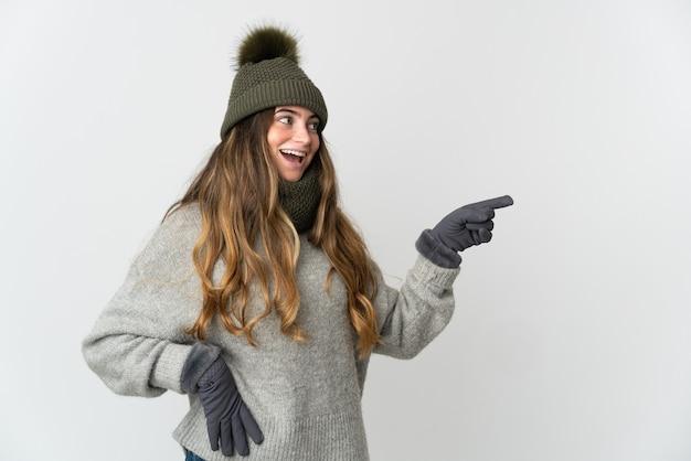 겨울 모자와 젊은 백인 여자는 측면에 손가락을 가리키고 제품을 제시하는 흰색 배경에 고립 프리미엄 사진