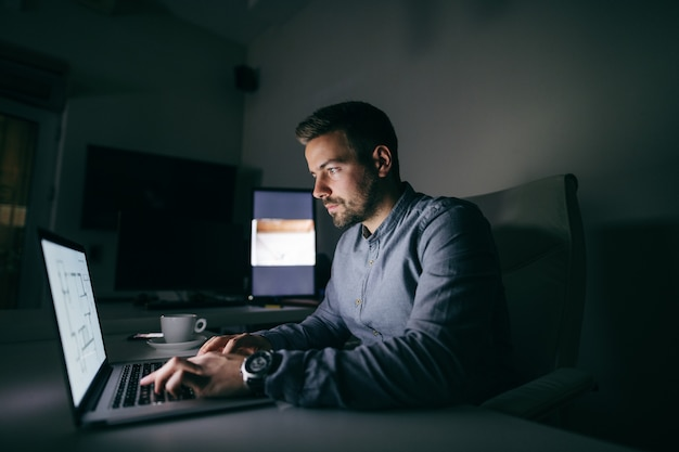 Young caucasian worker typing on laptop while sitting in the office late at night. Premium Photo