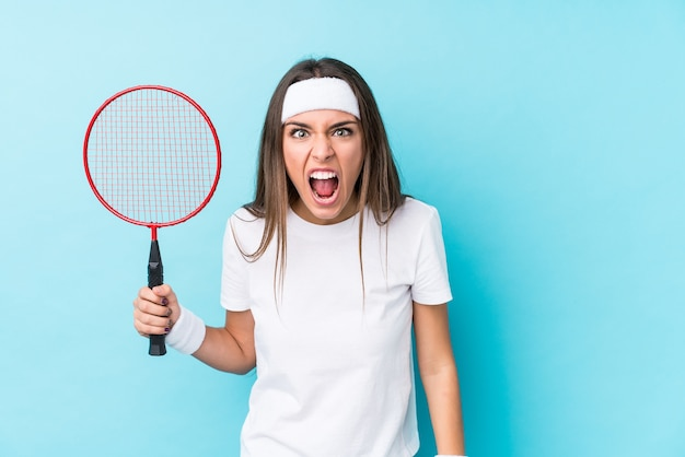 Молодая кавказская женщина, играющая в бадминтон, кричала очень сердито и агрессивно. Premium Фотографии