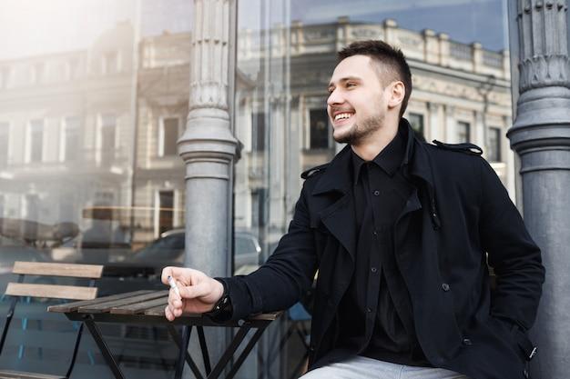 Sigaretta fumatori di giovane uomo allegro, sorridendo allegramente, guardando lontano. Foto Gratuite