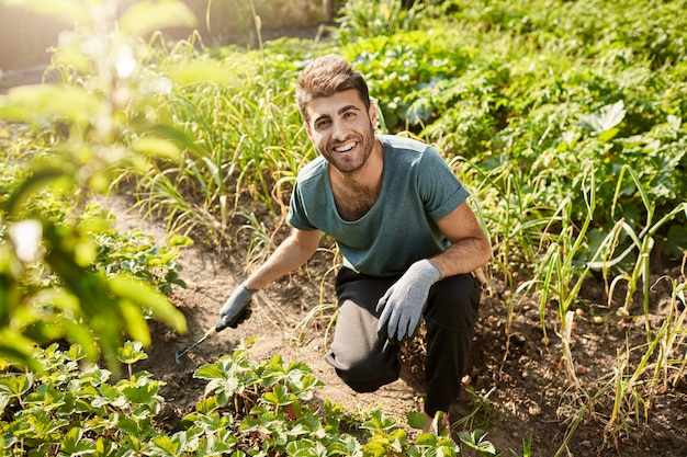 Giovane giardiniere maschio barbuto attraente allegro in maglietta blu e pantaloni sportivi neri sorridente, lavorando in giardino, piantando germogli con la pala. Foto Gratuite