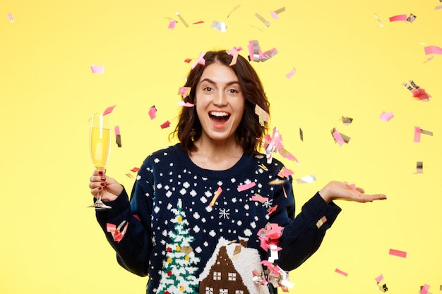 Young cheerful beautiful brunette girl in cosy knited sweater smiling holding glass of champagne over yellow background with falling confetti. Free Photo