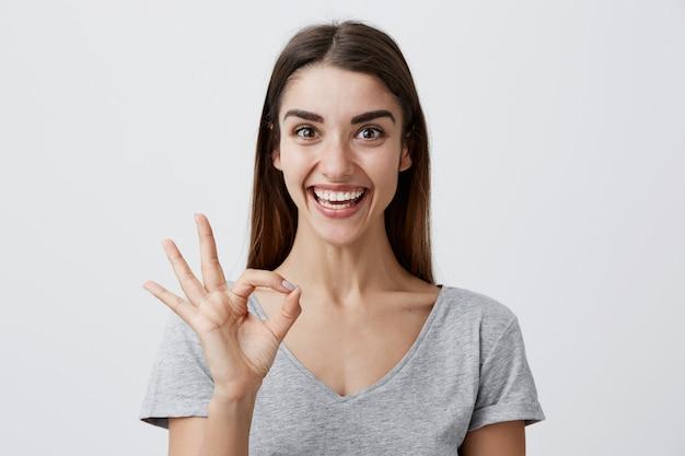 幸せで興奮した表情で、指でokサインを作るカジュアルな灰色のシャツに歯を浮かべて黒い長い髪を持つ陽気な美しい白人少女。コピースペース。 無料写真