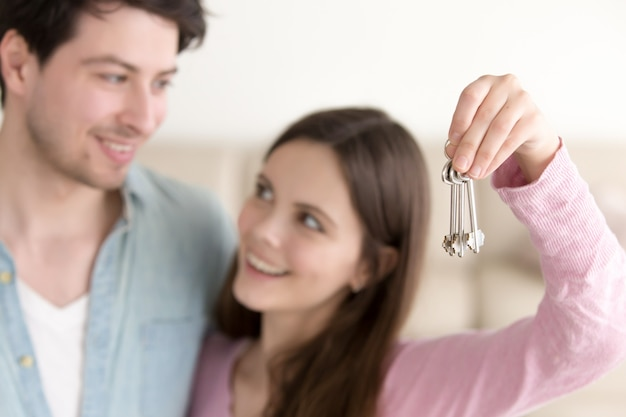 Young cheerful couple holding new house keys Free Photo