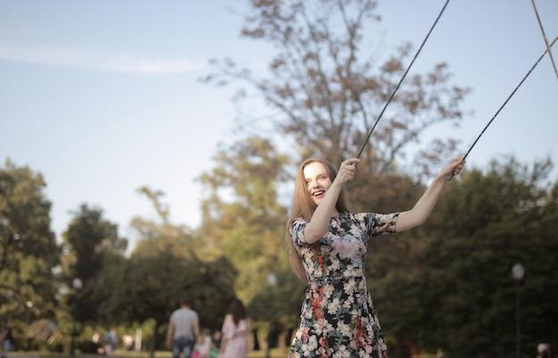 Молодая веселая женщина в парке под солнечным светом Бесплатные Фотографии