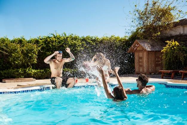 Young cheerful friends smiling, laughing, relaxing, swimming in pool Free Photo