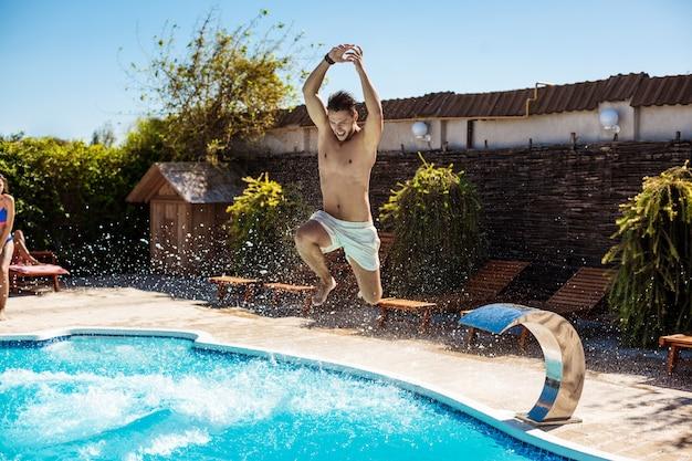 Giovani amici allegri che sorridono, che si rilassano, che saltano nella piscina Foto Gratuite