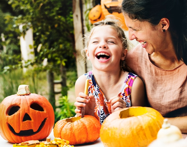 Young cheerful girl carving pumpkins with her mom Free Photo