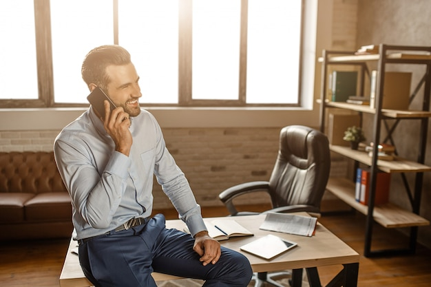 Young cheerful handsome businessman sit on table and talk on phone in his own office. he smile. business talk. confident and sexy. Premium Photo