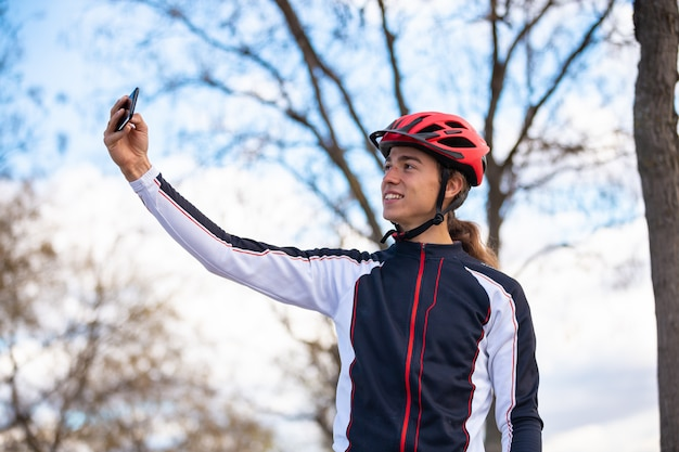 Young cheerful male cyclist in sportswear and helmet taking selfie on smartphone in park Premium Photo