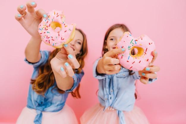 Молодая веселая мать и милая улыбающаяся дочь весело с вкусными пончиками в ожидании чаепития с семьей. маленькая девочка с мамой показывают пончики, которые они вместе приготовили, и смеются Бесплатные Фотографии