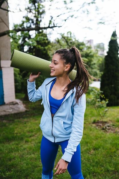 フィットネス敷物を保持している都市公園を歩いて若い陽気なスポーツ女性。 無料写真
