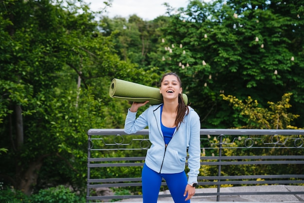 フィットネスラグを保持している都市公園を歩く若い陽気なスポーツ女性。 無料写真