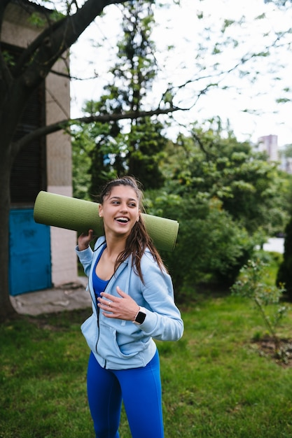 Young cheerful sports woman walking in urban park holding fitness rug. Free Photo