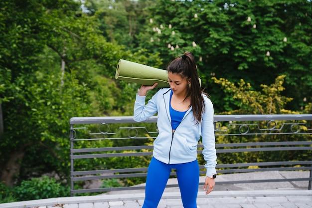Giovane donna sportiva allegra che cammina nel parco urbano che tiene tappeto fitness. Foto Gratuite