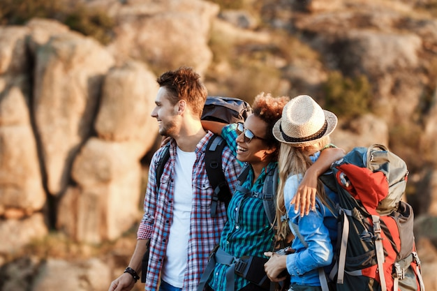 Young cheerful travelers with backpacks smiling, embracing, walking in canyon Free Photo