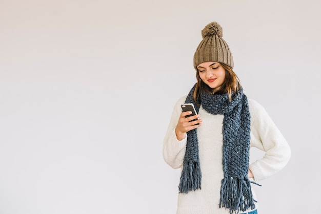 Young cheerful woman in hat and scarf with smartphone Free Photo