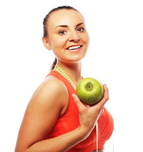アップル、白い背景で隔離のスポーツウェアの若い陽気な女性 Premium写真