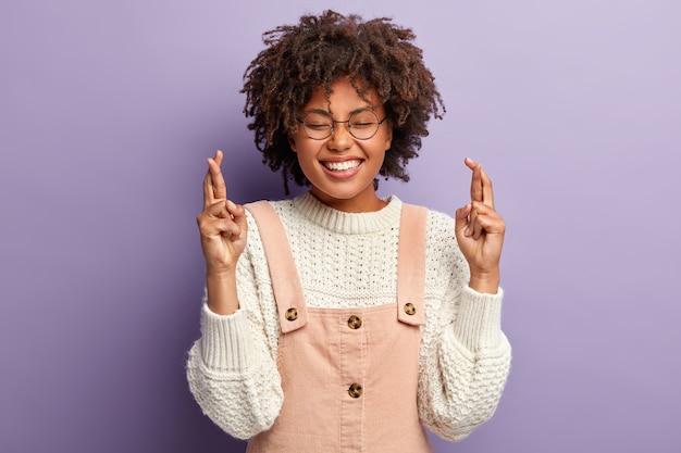 La giovane donna allegra tiene le dita incrociate, spera per il meglio, sorride ampiamente, indossa un maglione e una tuta bianca, esprime desideri, prega per i parenti, vuole raggiungere l'obiettivo, isolato sul muro viola Foto Gratuite