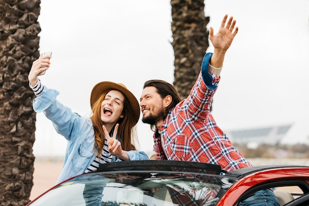 Young cheerful woman and man leaning out from car and taking selfie on smartphone Free Photo
