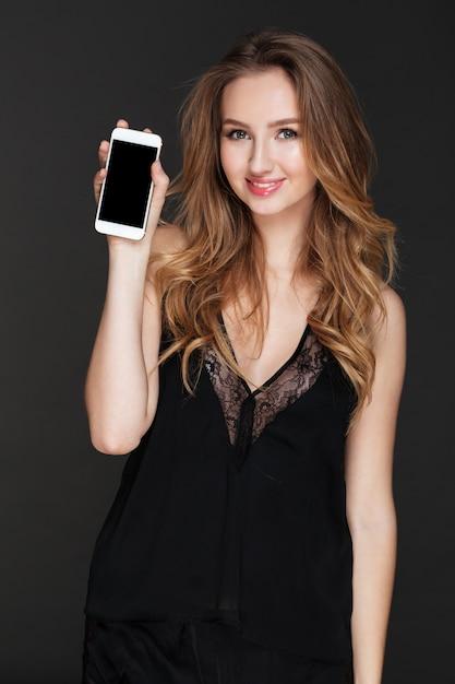 Giovane donna allegra che mostra l'esposizione del telefono alla macchina fotografica. Foto Gratuite