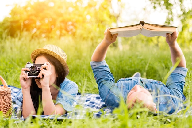 Young cheerful woman taking photo and man reading book in grass Free Photo