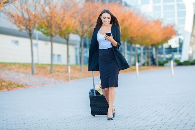 Young cheerful woman with a suitcase. the concept of travel, work, lifestyle Premium Photo