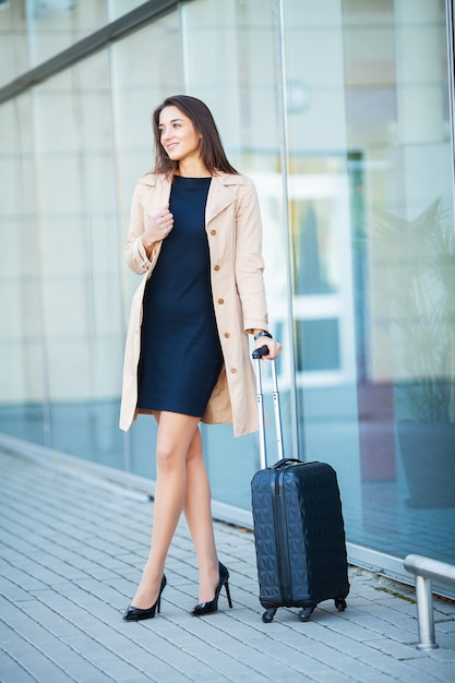 Young cheerful woman with a suitcase. the  of travel, work, lifestyle Premium Photo