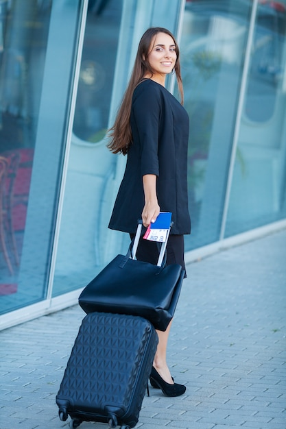 Young cheerful woman with a suitcase. Premium Photo