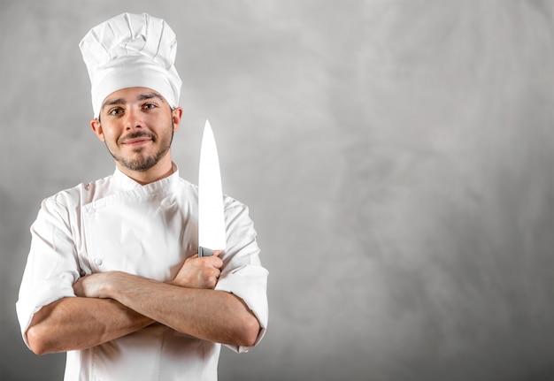 Молодой шеф-повар с ножом позирует с серой стены copyspace Premium Фотографии