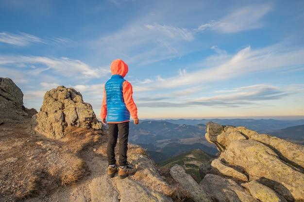 素晴らしい山の風景の景色を楽しみながら山に立っている幼児子供ハイカー。 Premium写真