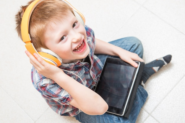 Young child is listening music with headphone on tablet Premium Photo