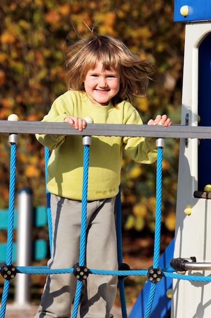 秋のカラフルな遊び場で遊ぶ幼児 無料写真