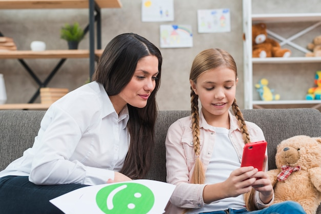 Young child psychologist looking at mobile phone hold by the little girl Free Photo