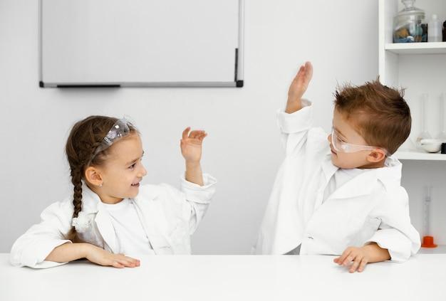 실험을하고 서로 하이 파이브하는 재미 어린 아이 과학자들 무료 사진