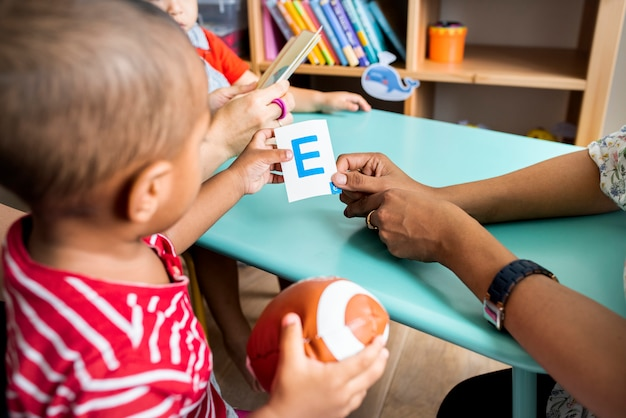 Young children learning the english alphabet with their parents Premium Photo