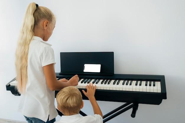 피아노 연주 방법을 배우는 어린 아이들 무료 사진